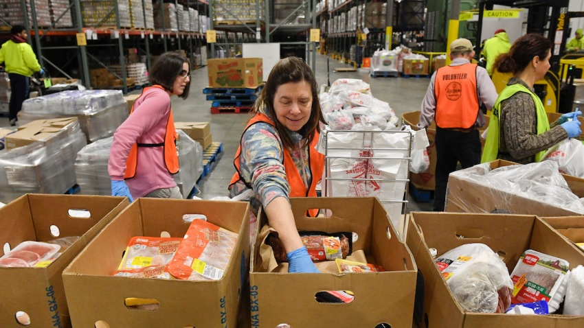 Kelly Schnur helps to load boxes at the Helping Harvest food bank