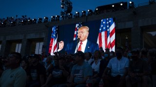 U.S. President Donald Trump is displayed on a screen as he speaks during an event at Mount Rushmore National Memorial in Keystone, South Dakota, U.S., on Friday, July 3, 2020.The early Independence Day celebration, which will feature a military flyover and the first fireworks in more than a decade, is expected to include about 7,500 ticketed guests who won't be required to wear masks or socially distance despite a spike in U.S. coronavirus cases.
