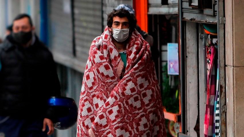 Transeúntes caminan frente a un comercio cerrado en la capital argentina.