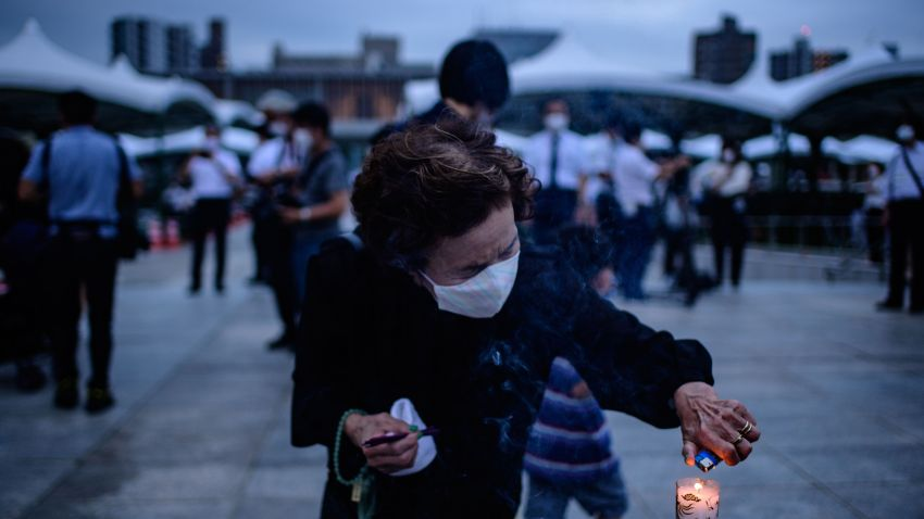 A visitor burns incense to pay tribute to the atomic bomb victims in front of the cenotaph at the Hiroshima Peace Memorial Park in Hiroshima on August 6, 2020 to mark 75 years since the world's first atomic bomb attack.
