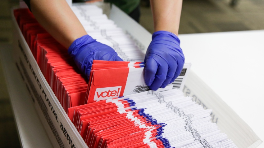 Election workers sort vote-by-mail ballots for the presidential primary