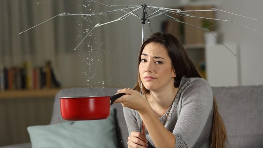 Foto de archivo de Shutterstock simula a una mujer con un paraguas roto y goteras en el techo.