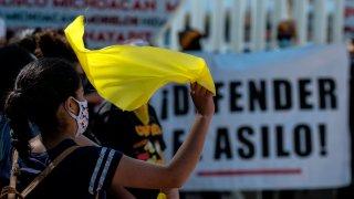 migrante con bandera amarilla protesta en la frontera