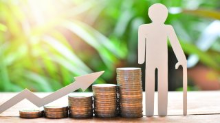 Monedas junto a una flecha ascendente y una silueta de cartón para simular a alguien con bastón. Foto concepto para ilustrar el ahorro para la jubilación.