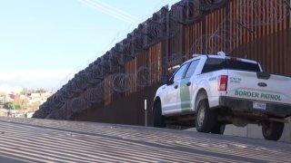 Border Patrol truck in front of the border wall
