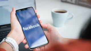 En la pantalla de un celular se ve el logo de la página de Facebook mientras una persona aguante el teléfono con sus dos manos.