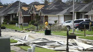 A person picks up debris damage near their home in Laplace, Louisiana, on August 30, 2021 after Hurricane Ida made landfall.